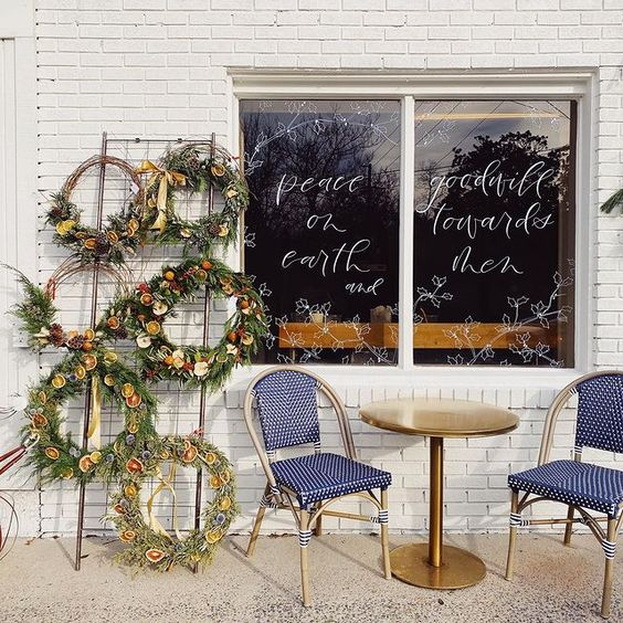 handmade wreaths and cafe chairs in front of a white brick wall and window that reads 'peace on earth, goodwill towards men' in script letters