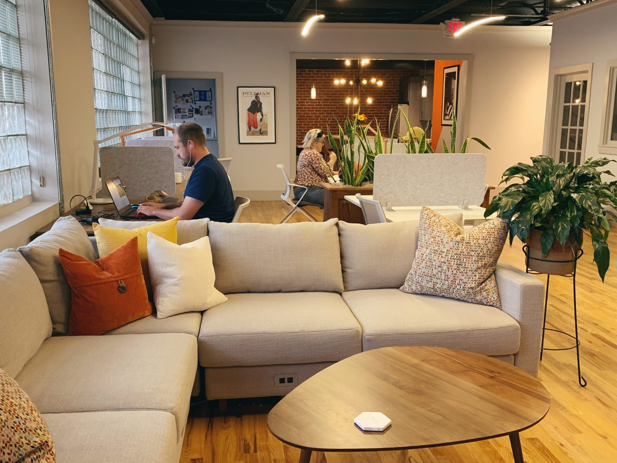people working at open desks in a coworking space