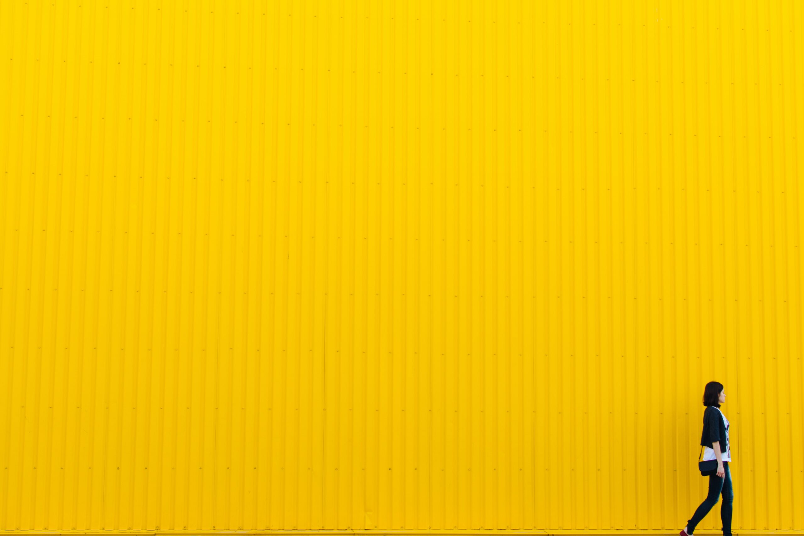 woman walks in front of a bright yellow wall
